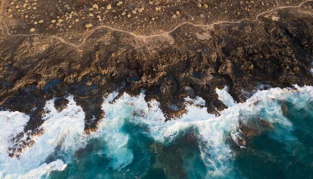 Luchtfoto van kliffen en schuim van zeegolven, canarische eilanden