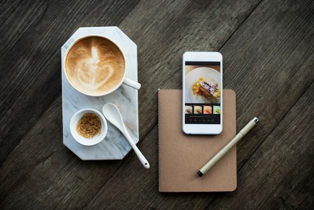 Luchtfoto van koffiekopje en mobiele telefoon op houten tafel