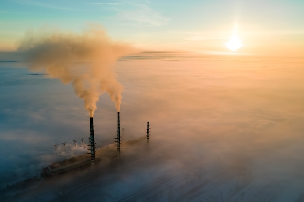 Luchtfoto van kolencentrale hoge pijpen met zwarte rook die vervuilende atmosfeer omhoog beweegt bij zonsondergang.
