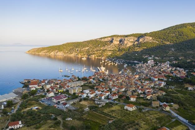 Luchtfoto van komiza stad op vis eiland, kroatië in dalmatië bij zonsopgang. stad die op kust in middellandse zee legt die door heuvels in de zomervakantie wordt omringd.