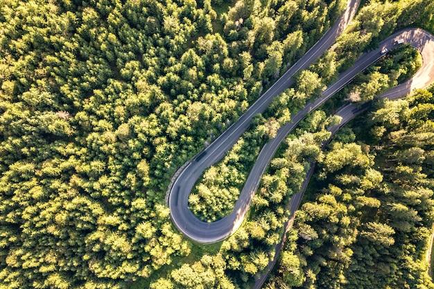 Luchtfoto van kronkelende weg in hoge bergpas trog dichte groene dennenbossen.