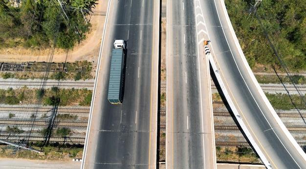 Luchtfoto van lading vrachtwagen op snelweg weg met blauwe container, transport concept., import, export logistieke industriële vervoer over land op de snelweg asfalt