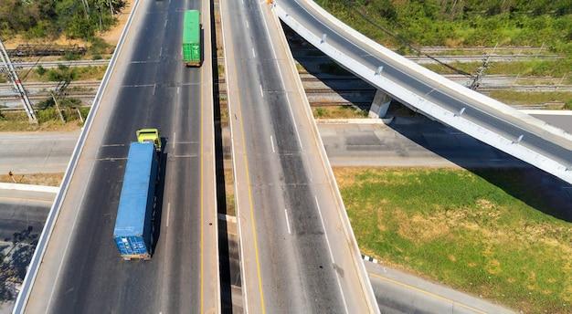 Luchtfoto van lading vrachtwagen op snelweg weg met blauwe en groene container, transport concept., import, export logistieke industriële vervoer over land op de snelweg asfalt