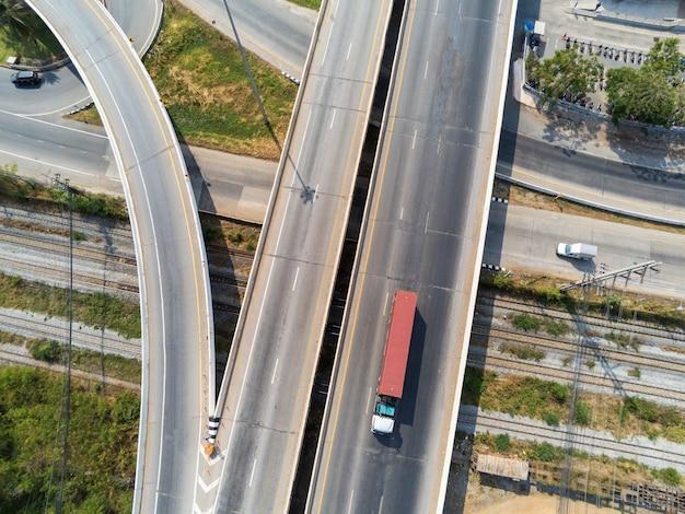 Luchtfoto van lading vrachtwagen op snelweg weg met rode container, transport concept., import, export logistieke industriële vervoer over land op de snelweg asfalt