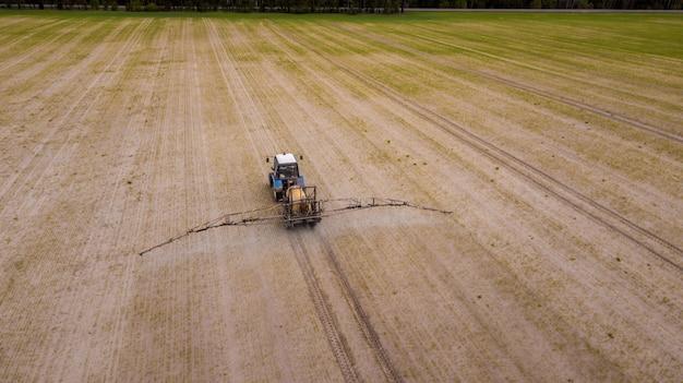 Luchtfoto van landbouwtractor ploegen en spuiten op veld