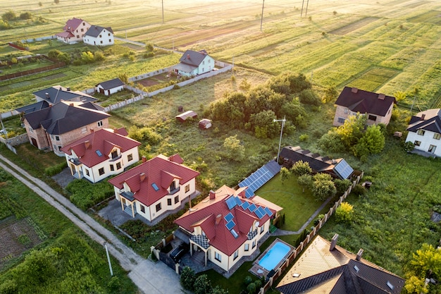 Luchtfoto van landelijke woonwijk met particuliere woningen tussen groene velden bij zonsopgang.
