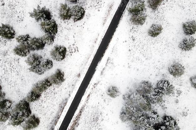 Luchtfoto van lege besneeuwde weg in de winterbos.