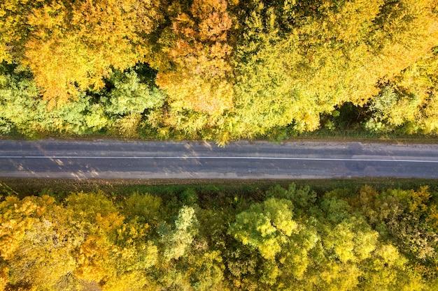 Luchtfoto van lege weg tussen gele herfstbomen.