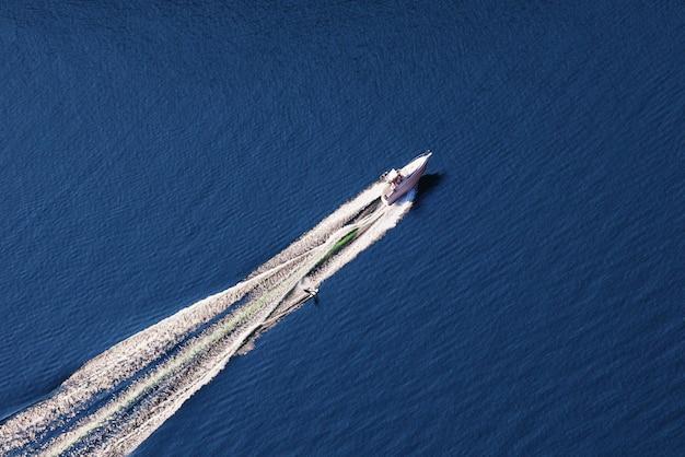 Luchtfoto van man wakeboarden op meer. waterskiën op meer achter een boot.