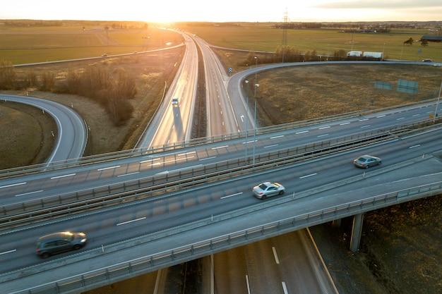 Luchtfoto van moderne snelweg weg kruispunt bij zonsopgang op landelijk landschap en het verhogen van de zon drone fotografie.