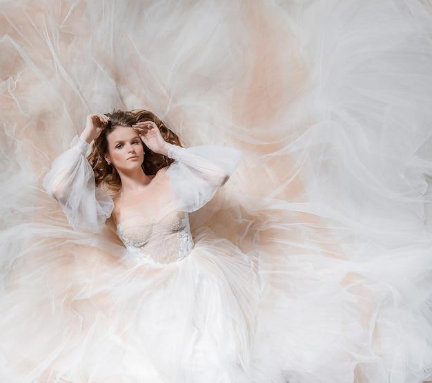 Luchtfoto van mooie jonge bruid die op de grond ligt en naar de camera kijkt, rondom in chiffon