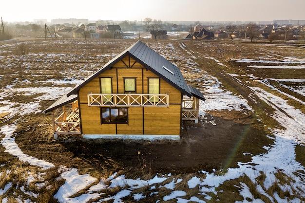 Luchtfoto van nieuwe houten ecologische traditionele huis cottage van natuurlijke hout materialen met steile grind dak in aanbouw op landelijk landschap