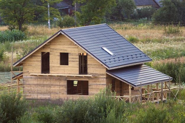 Luchtfoto van nieuwe houten ecologische traditionele huis huisje van natuurlijke hout materialen met zoldervloer, veranda, balkon en schindeldak in aanbouw in landelijk gebied.