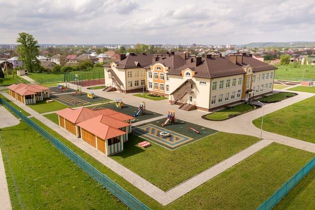 Luchtfoto van nieuwe prescool gebouw in residentiële landelijke omgeving.