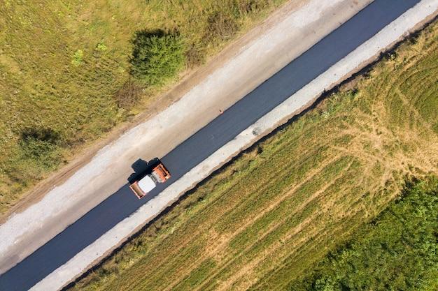 Luchtfoto van nieuwe wegenbouw met stoomwalsmachine op het werk.
