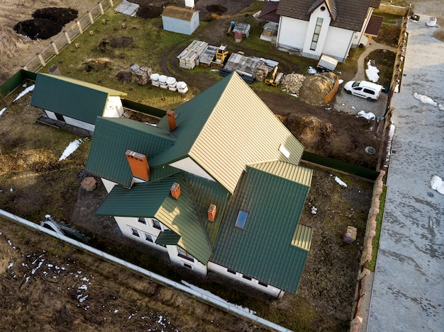 Luchtfoto van nieuwe woonhuis cottage en garage of schuur met shingledak op omheinde tuin op zonnige dag.