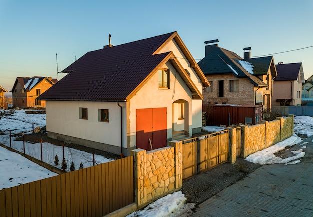 Luchtfoto van nieuwe woonhuis huisje en aangebouwde garage met schindeldak op omheinde tuin op zonnige winterdag in moderne buitenwijk. perfecte investering in droomhuis.