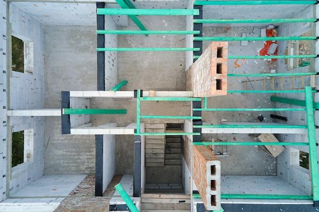 Luchtfoto van onafgewerkt frame van woonhuis met beluchte lichtgewicht betonnen muren en houten dakbalken in aanbouw.