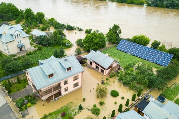 Luchtfoto van ondergelopen huis met vuil water eromheen.