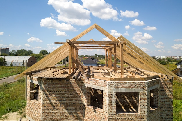Luchtfoto van onvoltooid huis met houten dak frameconstructie in aanbouw.