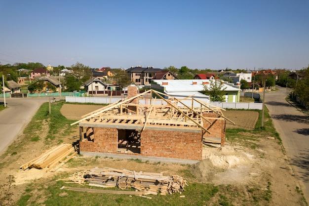 Luchtfoto van onvoltooide bakstenen huis met houten dak frameconstructie in aanbouw.