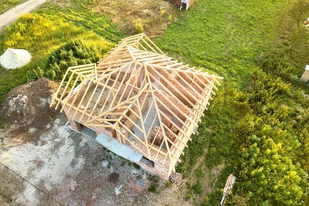 Luchtfoto van onvoltooide bakstenen huis met houten dakconstructie in aanbouw.