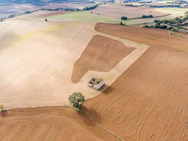 Luchtfoto van oude boerenhut en eenzame boom op gecultiveerd veld