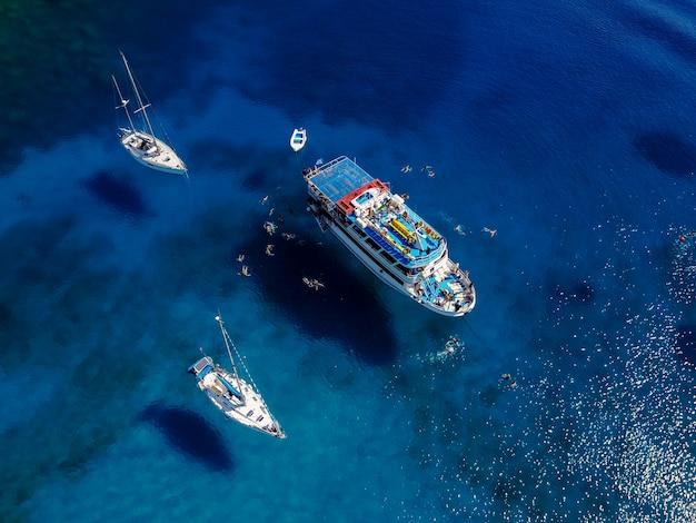 Luchtfoto van prachtige blauwe lagune op hete zomerdag met zeilboot. bovenaanzicht van mensen zwemmen rond de boot.