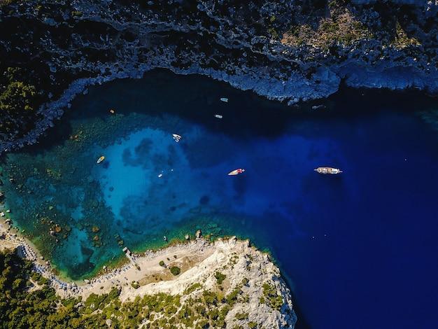 Luchtfoto van prachtige blauwe lagune op hete zomerdag met zeilboot. bovenaanzicht.