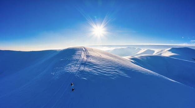Luchtfoto van prachtige winterberghellingen bedekt met sneeuw en sparrenbos op een zonnige wolkenloze dag. europees skiresort schoonheidsconcept