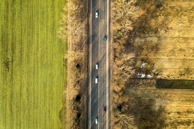 Luchtfoto van rechte weg met bewegende auto's, bomen en groene velden op zonnige dag. drone fotografie.