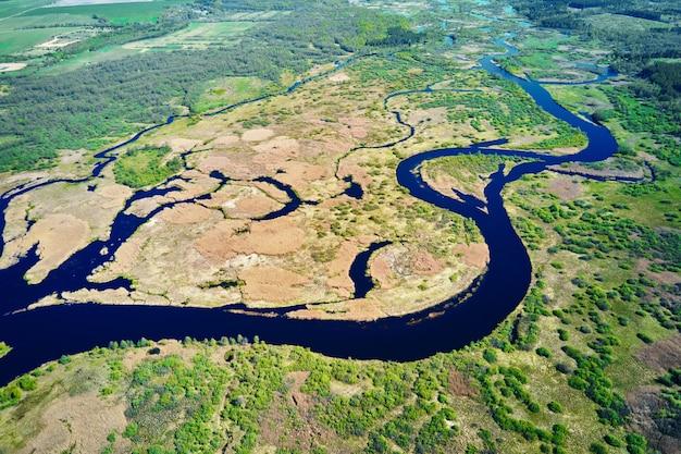 Luchtfoto van rivieroverstromingsplan en groen bos in zomerdag. vogelperspectief van het prachtige natuurlandschap