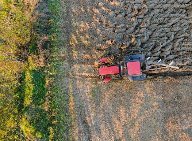 Luchtfoto van rode tractor ploegen veld in de herfst op de avond bij zonsondergang.