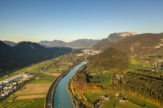 Luchtfoto van snelweg interstate weg met snel bewegend verkeer in de buurt van grote rivier in de bergen van de alpen