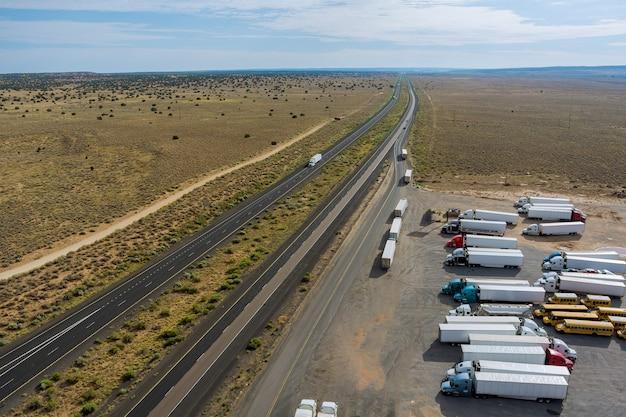 Luchtfoto van snelweg rustplaats met grote parkeerplaats voor auto's vrachtwagens bovenaanzicht van snelweg in woestijn een...