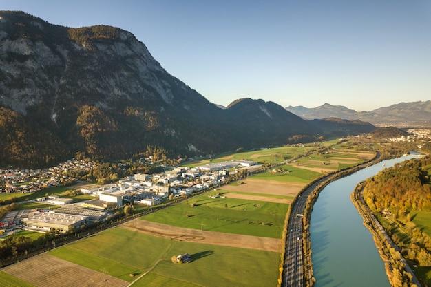 Luchtfoto van snelweg snelweg tusen staten met snel bewegend verkeer in de buurt van de grote rivier in de bergen van alpen