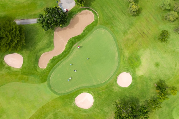 Luchtfoto van spelers op een groene golfbaan. golfspeler het spelen bij het zetten groen op een de zomerdag. mensen levensstijl ontspannen tijd in sportveld of vakantie buitenshuis activiteit.