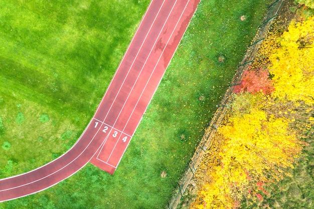 Luchtfoto van sportstadion met rode atletiekbanen met nummers erop en groen gras voetbalveld.