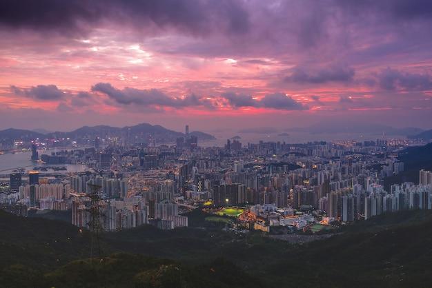 Luchtfoto van stadsgebouwen en wegen met lichten bij zonsondergang