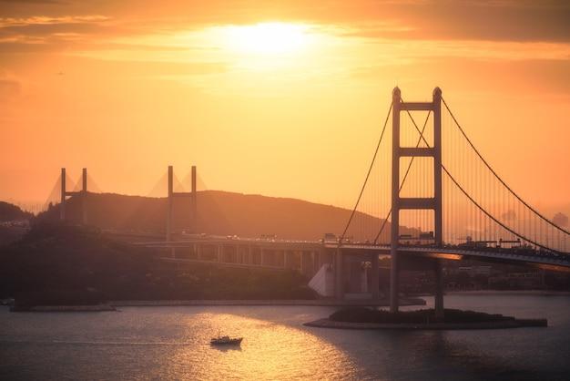 Luchtfoto van stadsgebouwen, heuvels en een brug over een rivier bij zonsondergang
