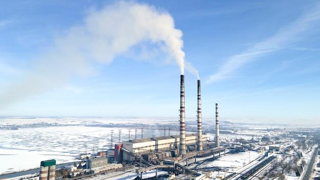 Luchtfoto van thermo-elektrische plant met grote schoorstenen in een landelijk landschap in de winter