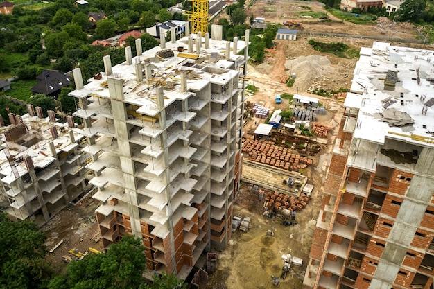 Luchtfoto van toren hijskraan en betonnen frame van hoge flat residentiële gebouwen in aanbouw in een stad