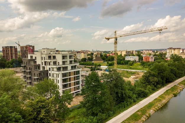 Luchtfoto van toren hijskraan en betonnen frame van hoog flatgebouw in aanbouw in een stad.