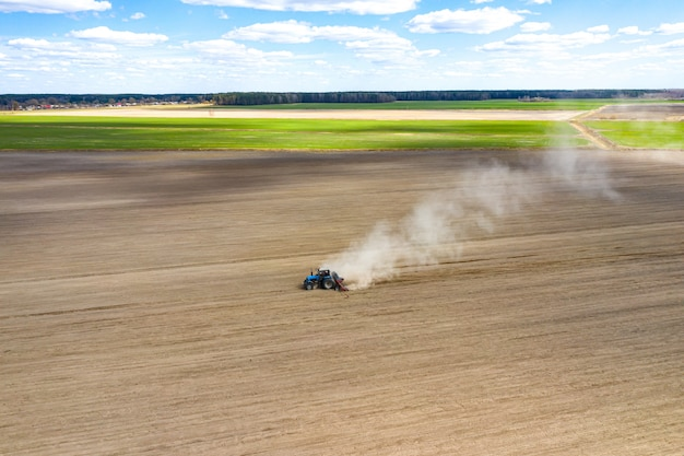 Luchtfoto van tractor met gemonteerde zaaimachine die direct zaaien van gewassen op geploegd landbouwgebied uitvoert. boer gebruikt landbouwmachines voor plantproces, bovenaanzicht
