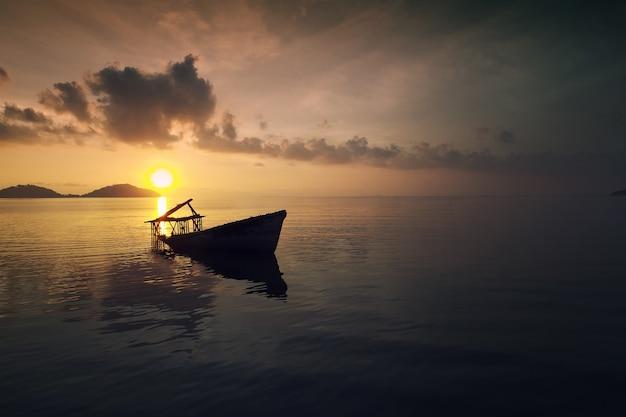 Luchtfoto van tropisch eiland en oude boot bij zonsondergang