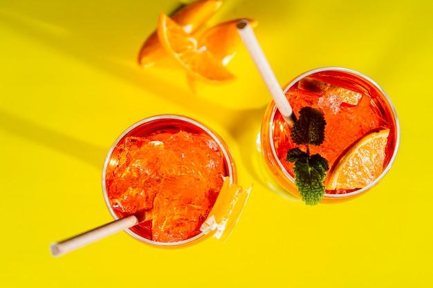 Luchtfoto van twee glazen van de italiaanse aperol spritz-cocktail met munt