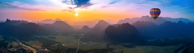 Luchtfoto van vang vieng met bergen en ballon bij zonsondergang.