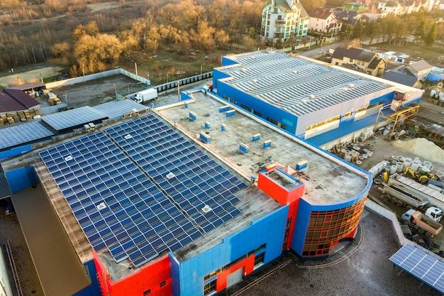 Luchtfoto van veel fotovoltaïsche zonnepanelen gemonteerd op het dak van een industrieel gebouw.
