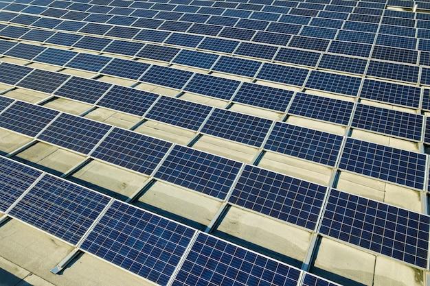 Luchtfoto van vele fotovoltaïsche zonnepanelen gemonteerd van industrieel gebouw dak.
