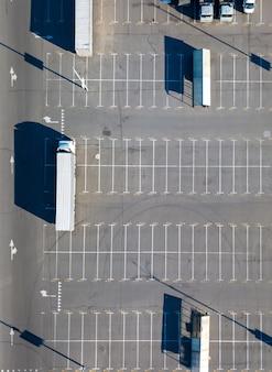 Luchtfoto van verschillende vrachtwagens op de parkeerplaats met schaduwen en lege parkeerplaatsen op een zomerdag